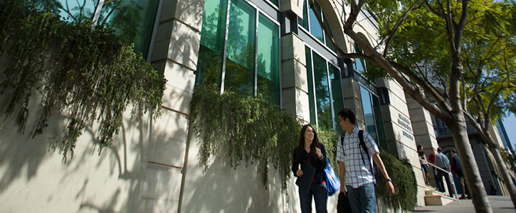 Two students walking outside of the library building