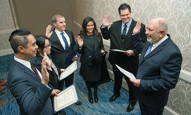 Federal District Judge Anthony Battaglia administers the oath to Jonathan Canlobo, Lianlian Wu, Steven Aicher, Cynthia Rodriguez Rosales and Brett Gunther