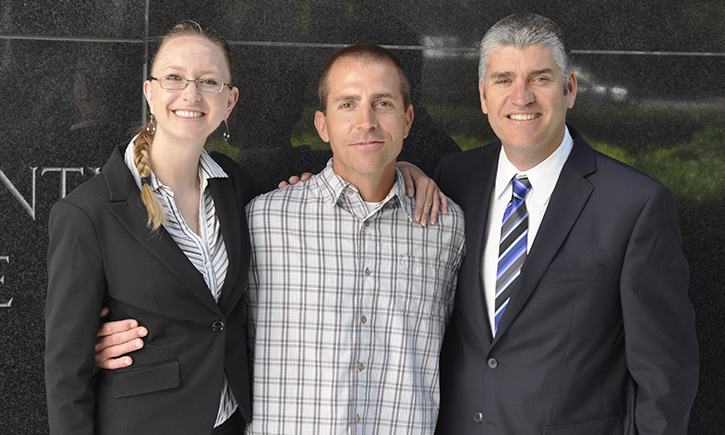 Uriah Courtney (center) with California Innocence Project Director Justin Brooks and attorney Alissa Bjerkhoel