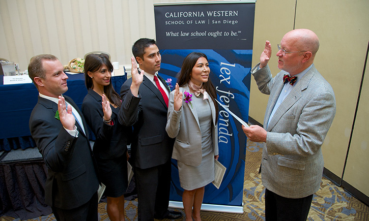 Hon. Michael B. Orfield '77 administers the Oath of Professional Conduct to California Western graduates William R. Jarrell, Sheela Tabrizi, Jeffrey P. Jackson, and Michelle L. Maisto