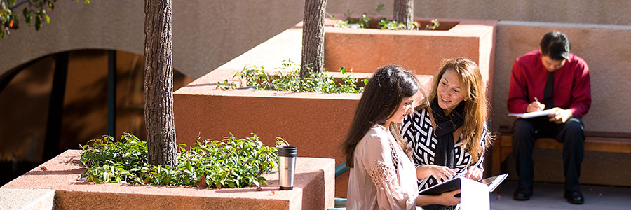 A professor talking with a student in the courtyard